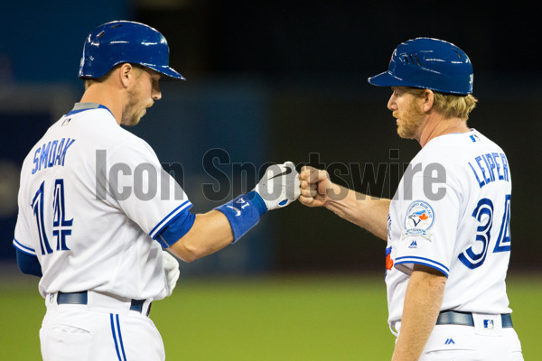 May 16, 2016:  Toronto Blue Jays first base coach Tim Leiper (34) fist pumps first baseman Justin Smoak (14) upon taking a walk in the first inning against the Tampa Bay Rays at the Rogers Center in Toronto, ON. (Photo by Kevin Sousa/Icon Sportswire)